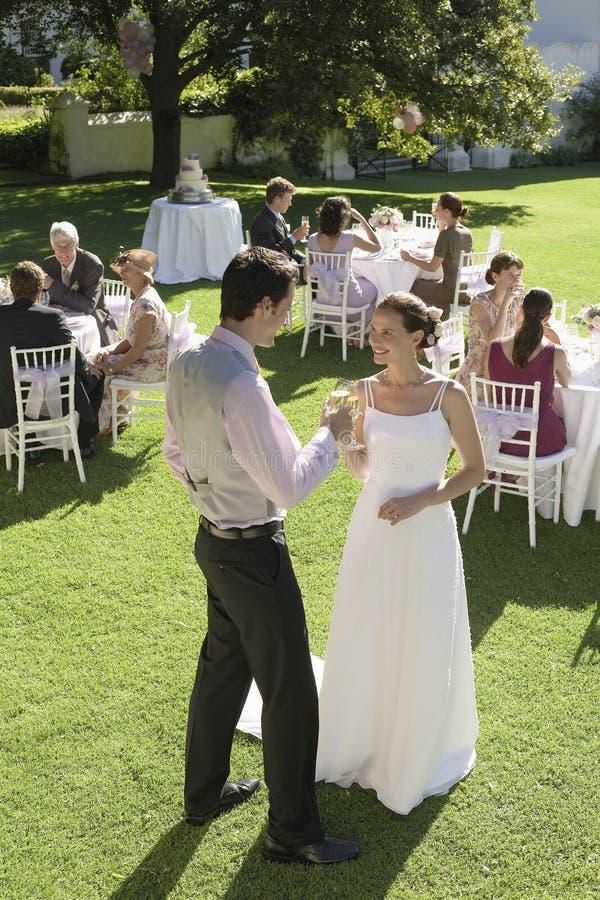 Nygift personpar som rostar Champagne In Garden arkivfoton