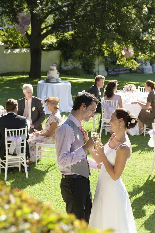 Nygift personpar som rostar Champagne Among Wedding Guests arkivbild