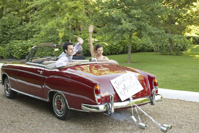 Nygift personpar som vinkar i cabriolet arkivfoton