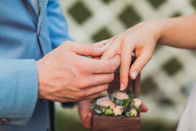 Nygift personutbytescirklar, brudgum sätter cirkeln på handen för brud` s royaltyfria foton