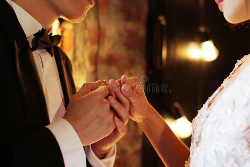 Nygift personutbytescirklar, brudgum sätter cirkeln på handen för brud` s i förbindelseregistreringskontor brun dark för bakgrund royaltyfri foto