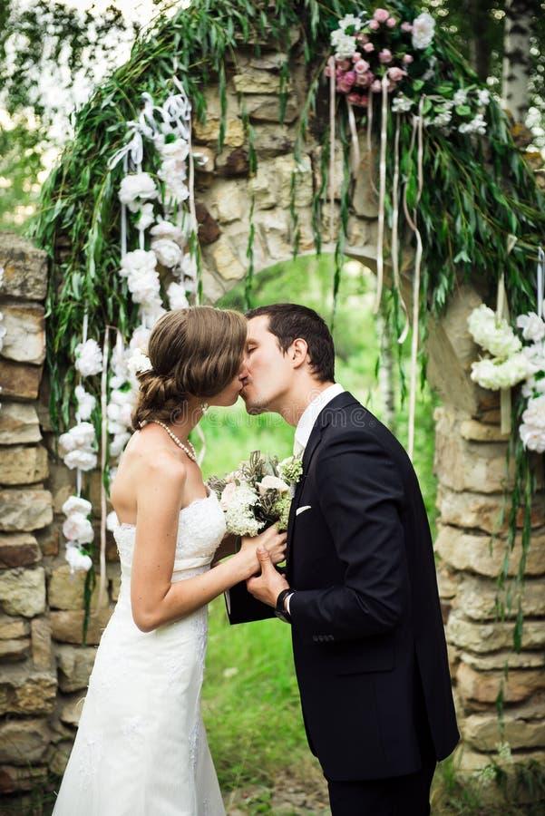 Nygifta personer är kyssande på den utvändiga bröllopceremonin royaltyfria foton