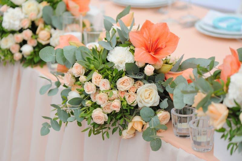 Nygifta personer bordlägger dekorerat med buketten och stearinljus arkivbilder
