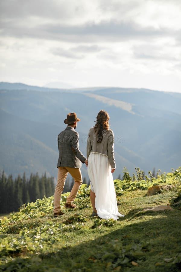 Nygifta personer går och rymmer händer i berg arkivfoton