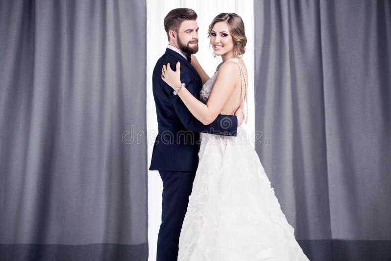 Nygifta personer i en bröllopsklänning och en dräkt royaltyfria bilder