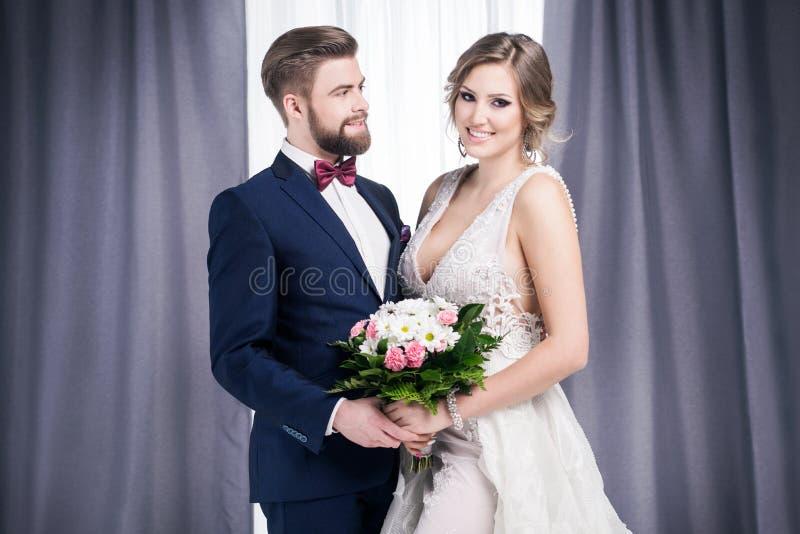 Nygifta personer i en bröllopsklänning och en dräkt royaltyfri bild