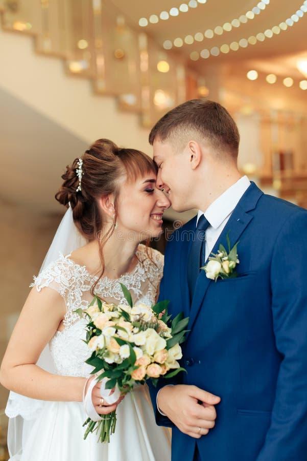 Nygifta personer i lägenheten, en härlig brud och brudgum i den rika inre 1en royaltyfria foton