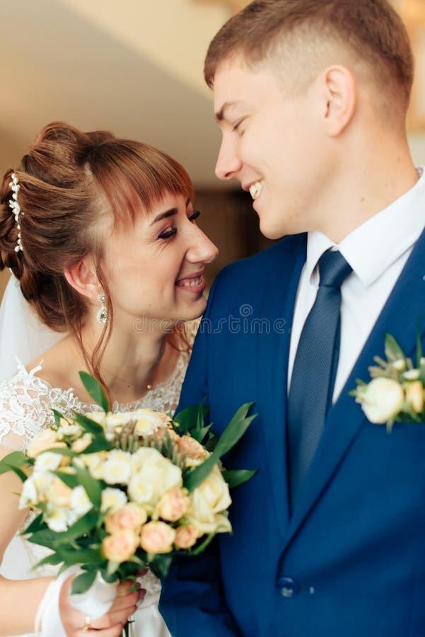 Nygifta personer i lägenheten, en härlig brud och brudgum i den rika inre 1en royaltyfri fotografi