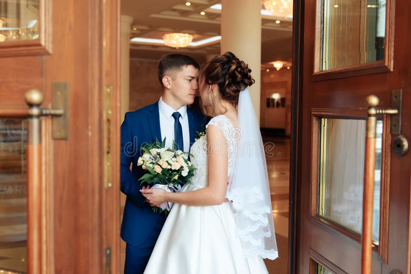 Nygifta personer i lägenheten, en härlig brud och brudgum i den rika inre 1en royaltyfri foto