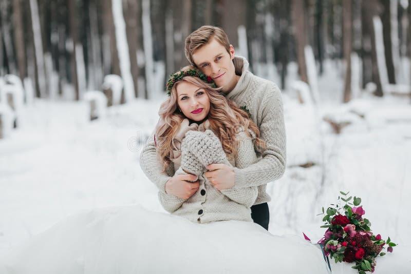 Nygifta personer kramar i de förälskade vinterskogparen Vinterbröllopceremoni arkivfoton