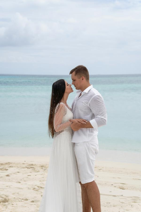 Nygifta personer kramar på en ursnygg strand med vitt sand- och turkosvatten arkivbilder
