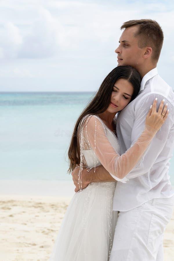 Nygifta personer kramar på en ursnygg strand med vitt sand- och turkosvatten fotografering för bildbyråer
