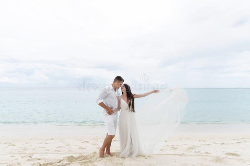 Nygifta personer kramar på en ursnygg strand med vitt sand- och turkosvatten royaltyfri fotografi