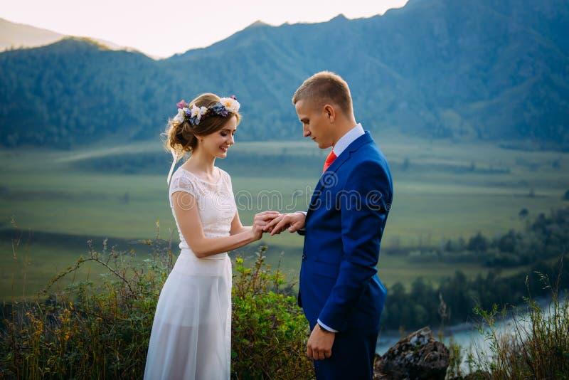 Nygifta personer på bröllopceremoni på bakgrund av berg Bruden är den iklädda klassiska vita bröllopsklänningen, brudgumme arkivfoton