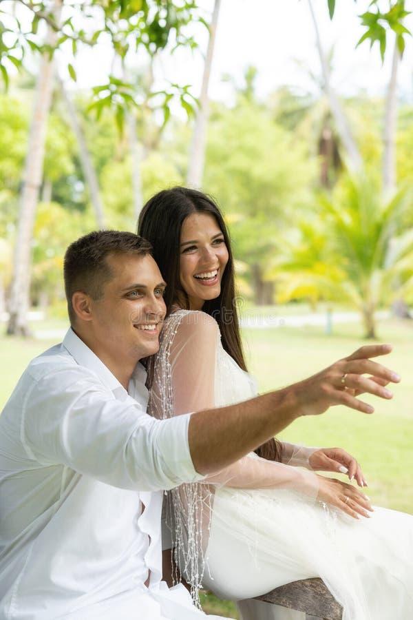 Nygifta personer skrattar och ser lyckligt in i en ljus framtid royaltyfri fotografi