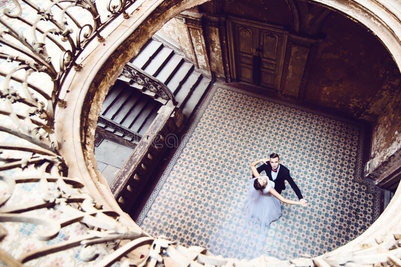Nygifta personer som dansar i ett gammalt hus arkivfoton