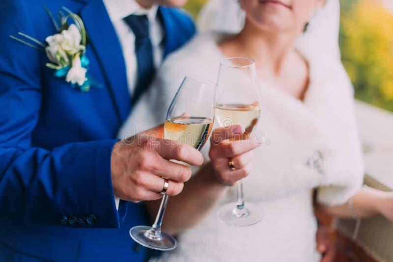 Nygifta personer som firar deras bröllop som dricker champagneanseende nära tegelstenväggen Närbild royaltyfri bild