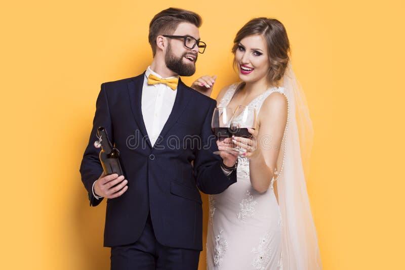 Nygifta personer som firar dricka rött vin royaltyfria foton