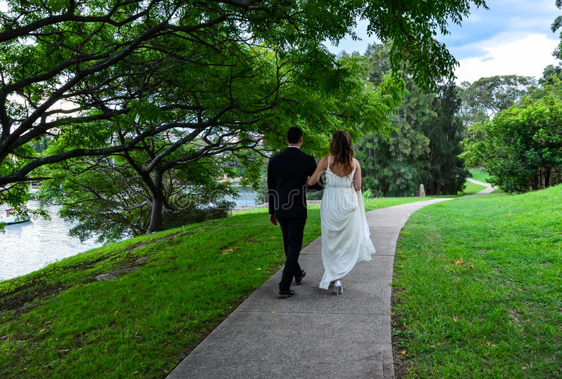 Nygifta personer som går armen i arm fotografering för bildbyråer