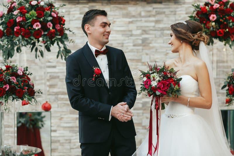 Nygifta personer som joyfuly ser de under ceremonin royaltyfria foton