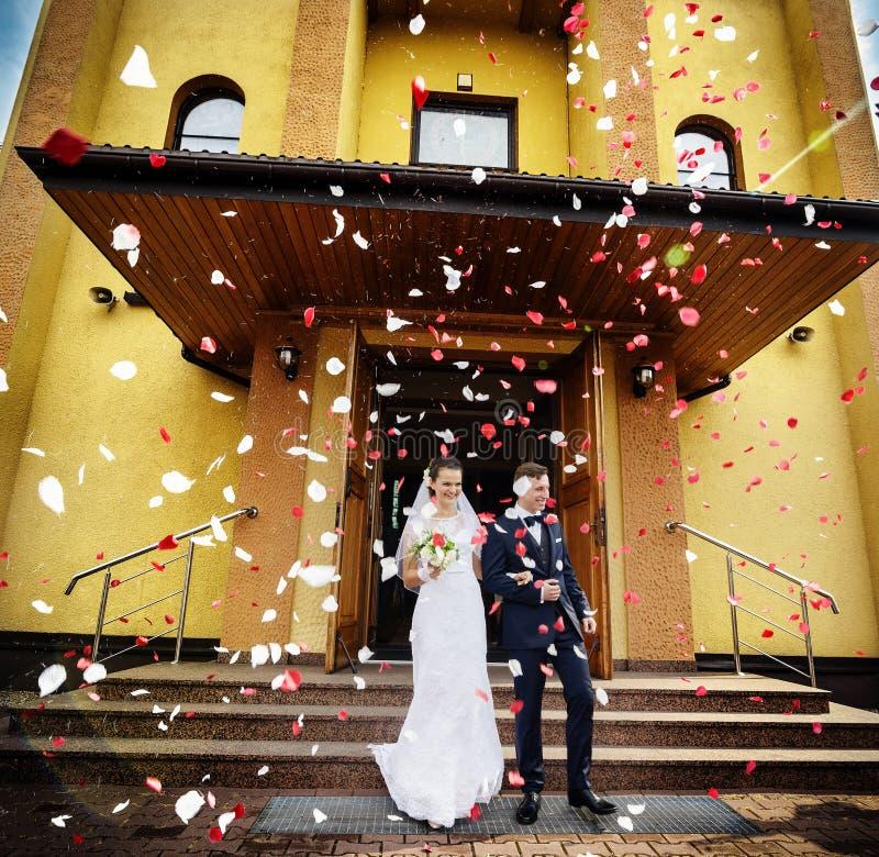 Nygifta personer som kommer ut ur kyrkan efter bröllopceremoni royaltyfri foto