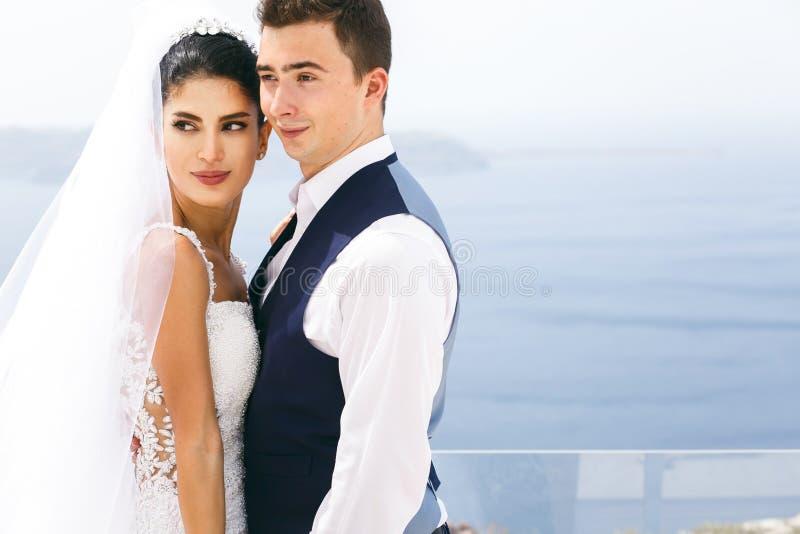Nygifta personer som kramar på havskust royaltyfri fotografi