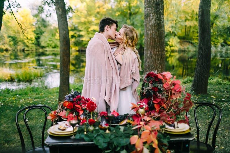 Nygifta personer som kysser under plädet bredvid den festliga tabellen Brud och brudgum i parken Höstbröllop artistically royaltyfri foto