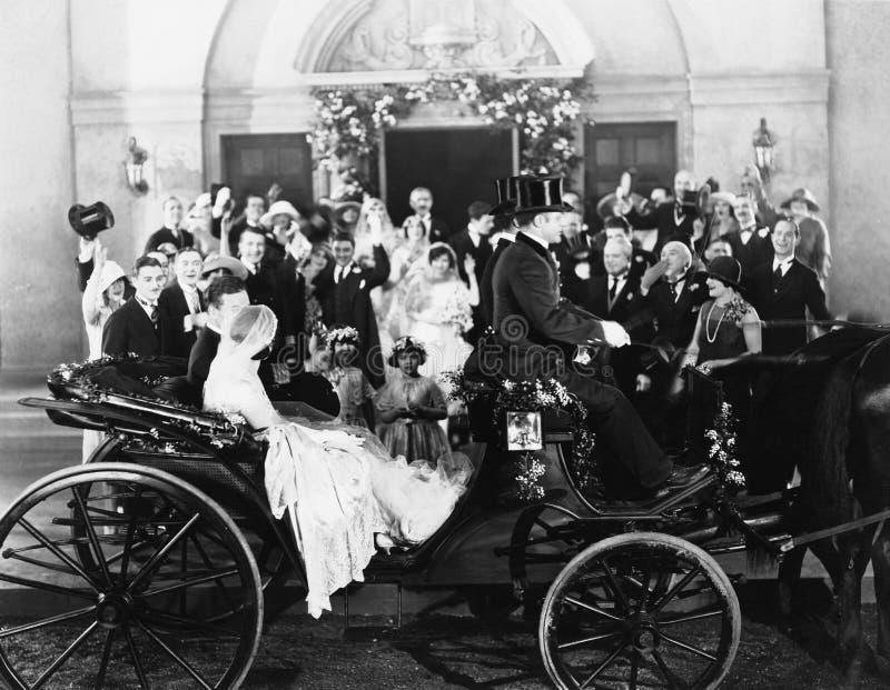 Nygifta personer som lämnar bröllop i vagn royaltyfria bilder
