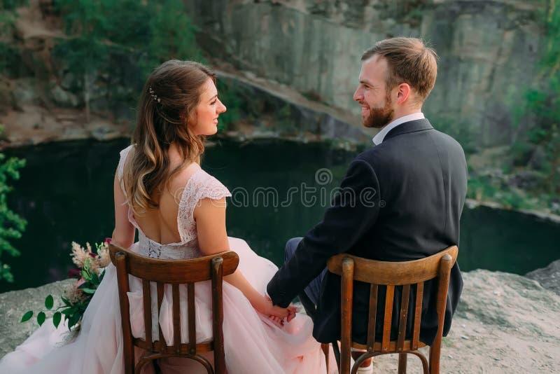 Nygifta personer som sitter på kanten av kanjonen och paren som ser sig med mjukhet och förälskelse Utomhus gifta sig arkivfoton