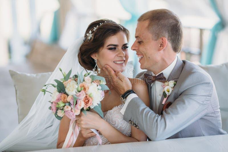 Nygifta personer som sitter på tabellen och krama Bruden och brudgummen ler se de En man i en grå färg royaltyfri foto