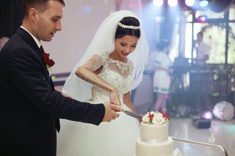 Nygifta personer som snider en läcker tiered vit bröllopstårta, dekorerar arkivbilder