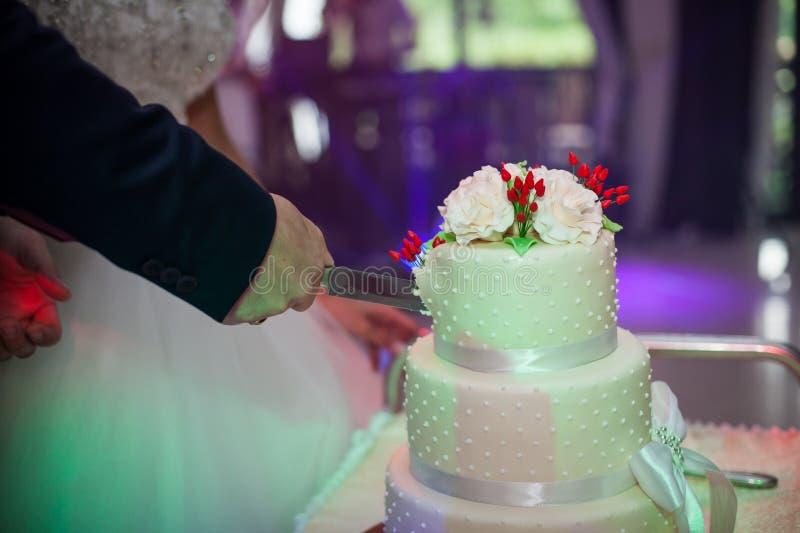 Nygifta personer som snider en läcker tiered vit bröllopstårta, dekorerar royaltyfria bilder