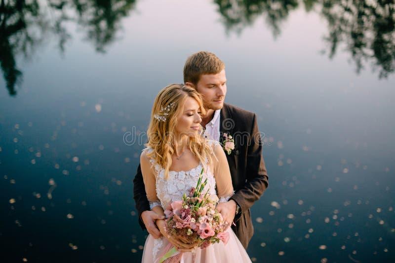 Nygifta personer som står på sjökusten på solnedgången arkivfoton
