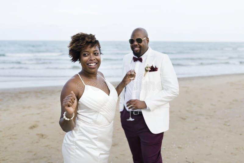 Nygifta personer som tycker om deras bröllopmottagande på stranden royaltyfri fotografi
