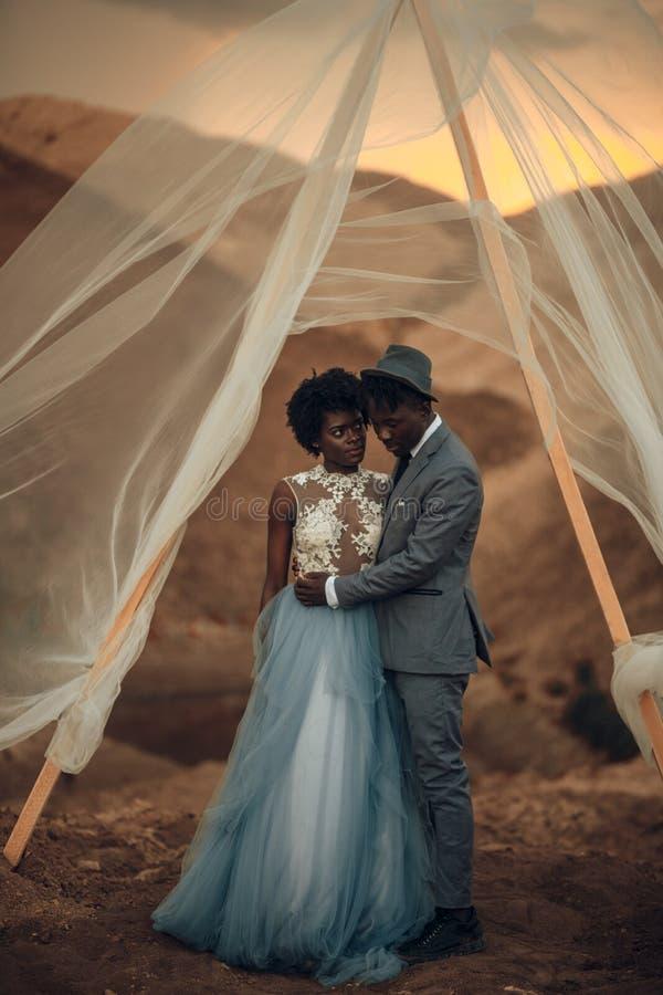 Nygifta personer står och omfamnar under brölloptältet i kanjon på solnedgången royaltyfri fotografi