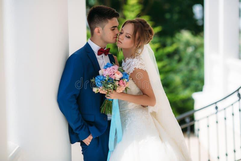 Nygifta personer strosar i en gräsplan parkerar med vita kolonner En man i en bröllopdräkt önskar att kyssa en flicka En kvinna i royaltyfri foto