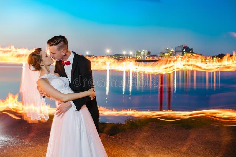 Nygifta personer vid sjön på natten arkivfoton