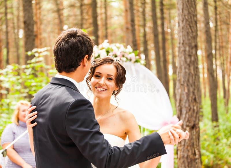 Nygifta personerna som dansar nära bröllopbågen arkivbilder