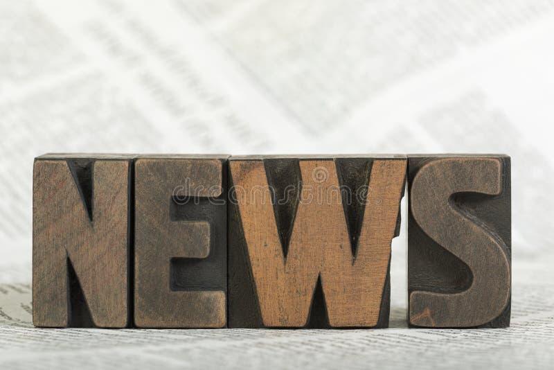 Nyheterna ord som är skriftligt med boktryck som skrivar ut kvarter på tidningen arkivfoton