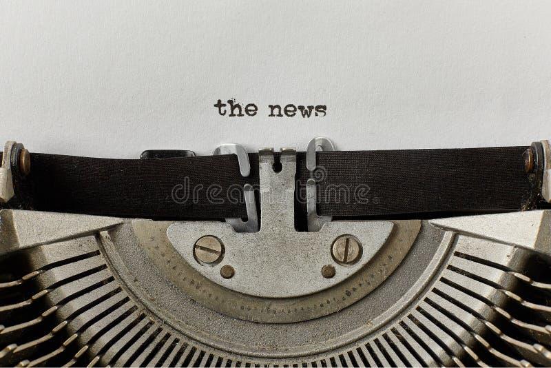 Nyheterna skrev ord på en tappningskrivmaskin arkivbilder