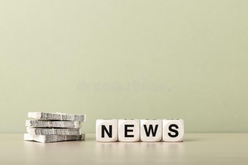 Nyheternabegrepp med tidningar och kub-bokstäver royaltyfri bild