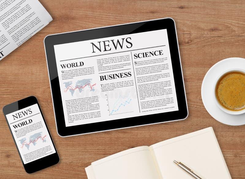 Nyheternasida på minnestavlan och mobiltelefonen royaltyfri bild