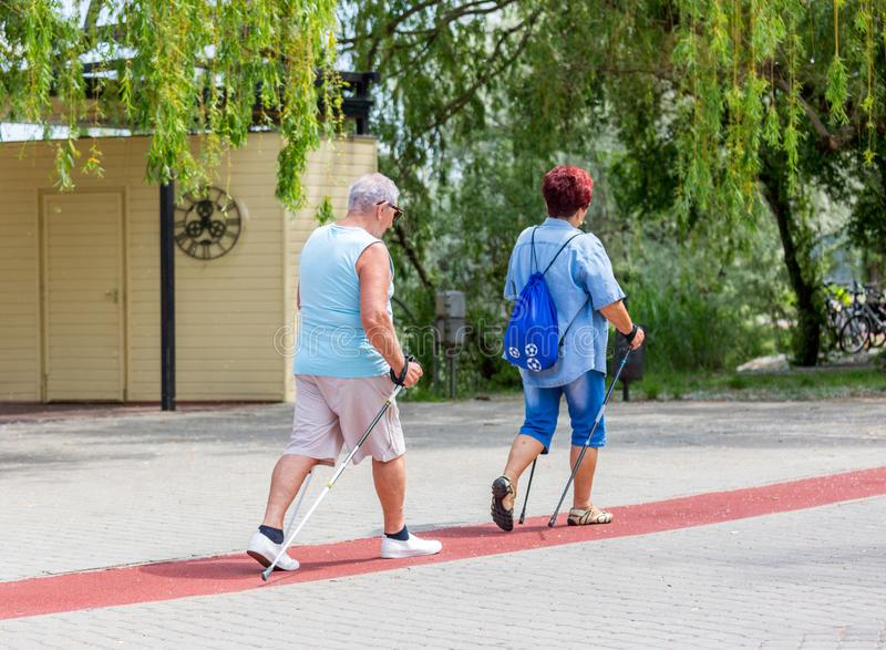 Senior couple walking with hiking sticks on treadmill along lake in city park stock images