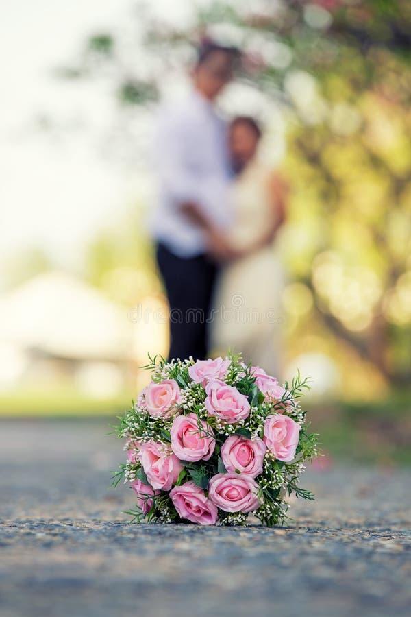 Nyligen gift par- och bröllopbukett i förgrunden royaltyfri foto