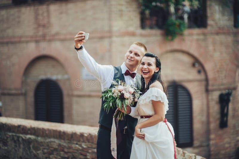 Nyligen gifta sig pardanandeselfie efter ceremoni royaltyfri fotografi