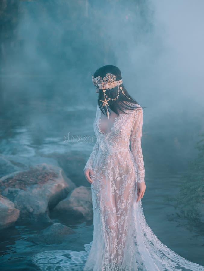 Nymfen går i floden som drogs åt av en tjock ogenomtränglig dimma Hon har en vit tappning, spets- klänning festmåltid royaltyfri fotografi