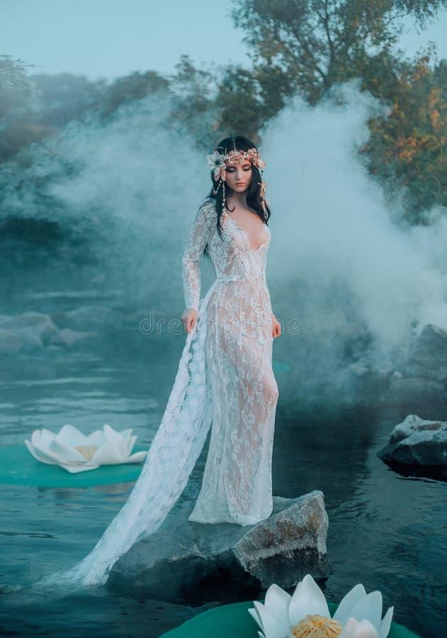 Nymfen med långt mörkt hår i en vit tappningklänning står på en sten i mitt av floden i håret a royaltyfri fotografi