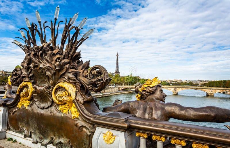 Nymfer av seinen förgyllde statyn på den Alexander III bron med Eiffeltorn i bakgrunden i Paris arkivfoto