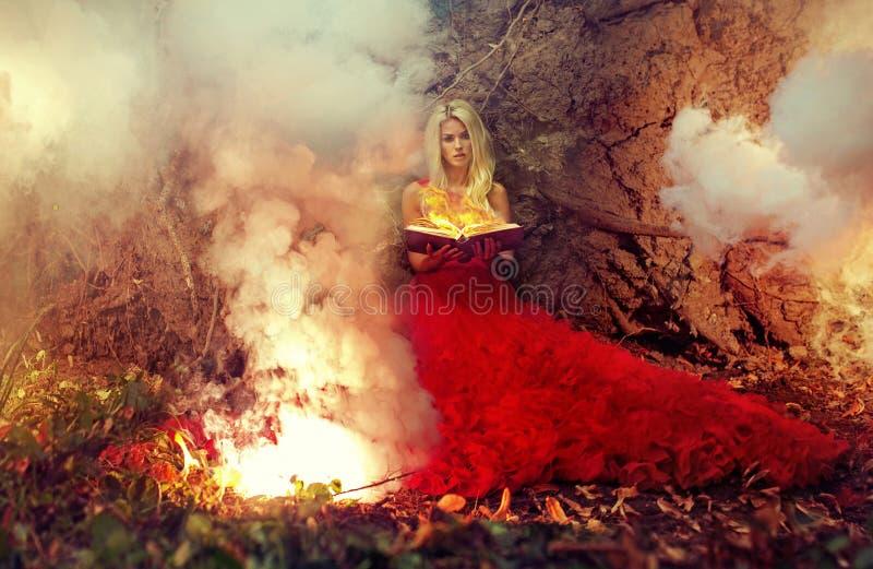 Nymphe blonde tenant le livre de magie de mise à feu photographie stock