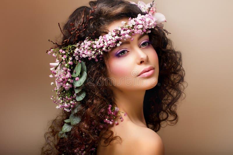 Nymphe. Entzückender sinnlicher Brunette mit Girlande der Blumen sieht wie Engel aus lizenzfreies stockbild